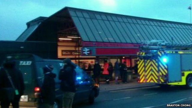 Emergency services and passengers outside Crewe station