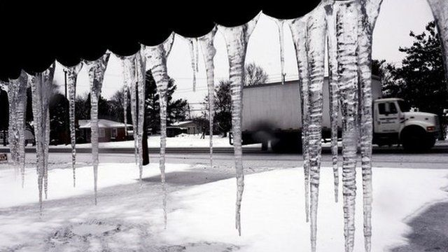 Icicles dangle from the metal awning at a home during a snow storm in Lumberton, North Carolina 12 February 2014