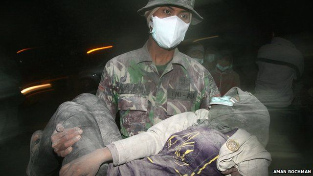 An Indonesian military soldier carries a collapsed resident during the evacuation following eruption of Mount Kelud