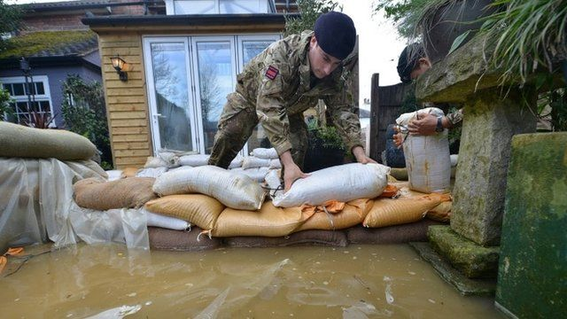 Soldier stacking sandbags outside flooded house