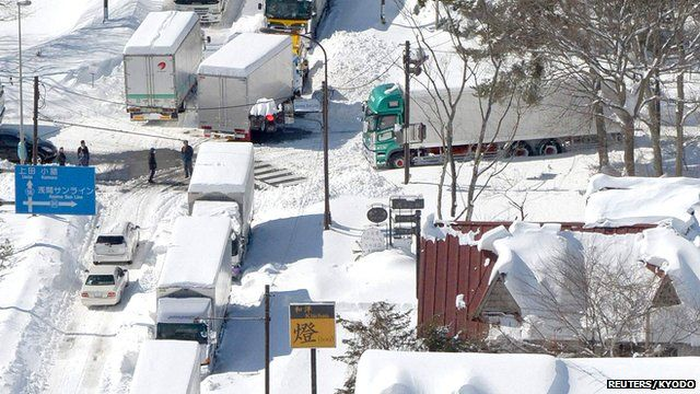 Trucks and cars are stranded by heavy snow on a national road in Karuizawa