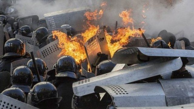 Flames erupt around Interior Ministry police during clashes with anti-government protesters in Kiev on Tuesday