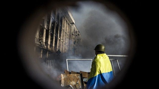 An anti-government protester wrapped in the Ukrainian national flag stands by a barricade during clashes with riot police on Kiev's Independence square on February 19, 2014
