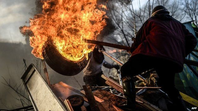 An anti-government demonstrator holds a burning tire