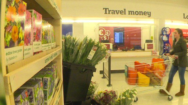 A lady pushes a trolley past a travel money counter in a supermarket