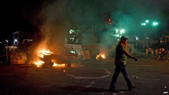A demonstrator walks near a car set on fire