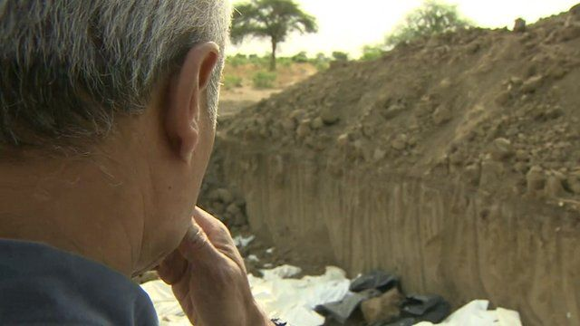 George Alagiah at the site of mass graves