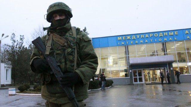 An armed man patrols at the airport in Simferopol, Crimea