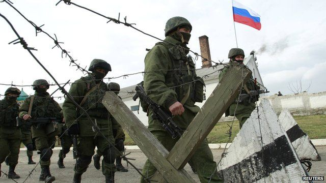 Russian troops march outside a Ukrainian military unit