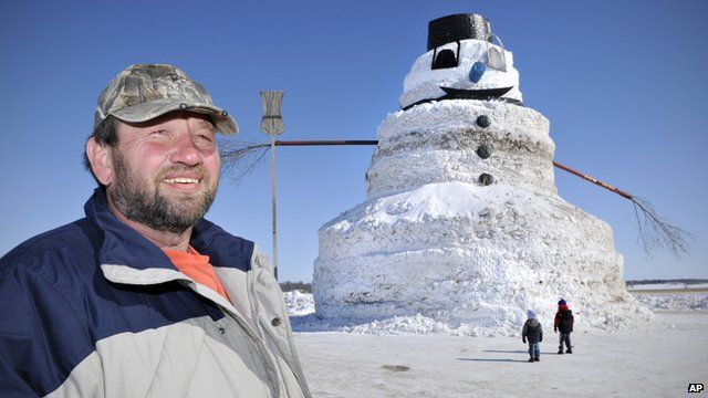 Greg Novak stands next to the giant 50-foot snowman