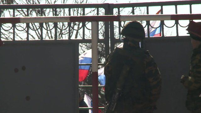 Soldiers inside the gates as Russian flags wave outside