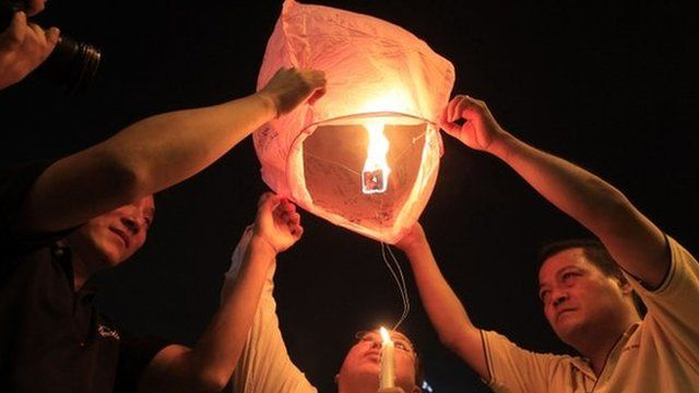 People prepare to release a sky lantern during a candlelight vigil for passengers
