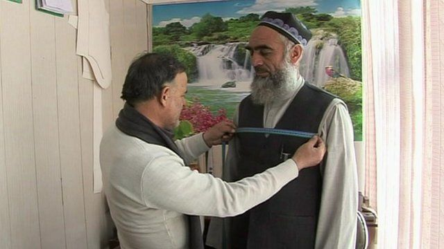 A Tajik Imam being fitted for a new robe