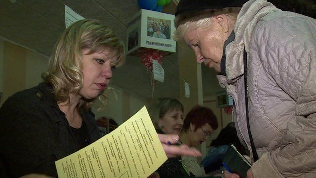 A voter at the polling station shows her passport
