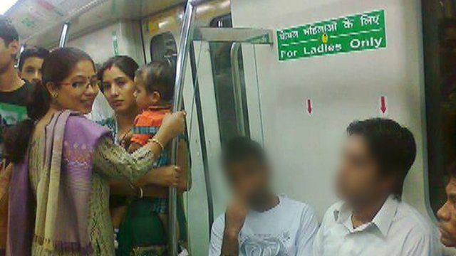 """Two men sitting in """"ladies-only"""" seats on the Delhi metro"""