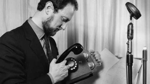 An old black and white photo showing a BBC studio manager recording the sound of an old phone