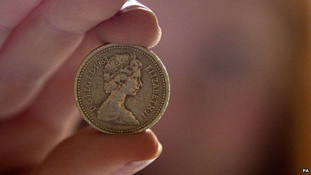Person holding a one pound coin