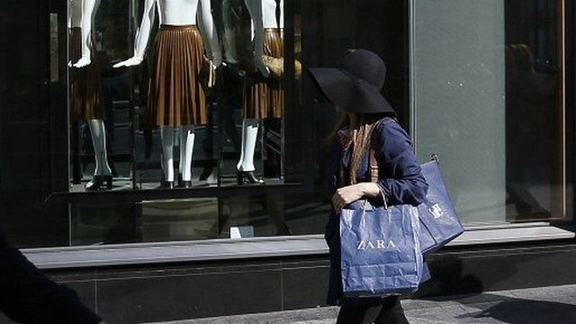A woman with Zara bag walks past a Zara store