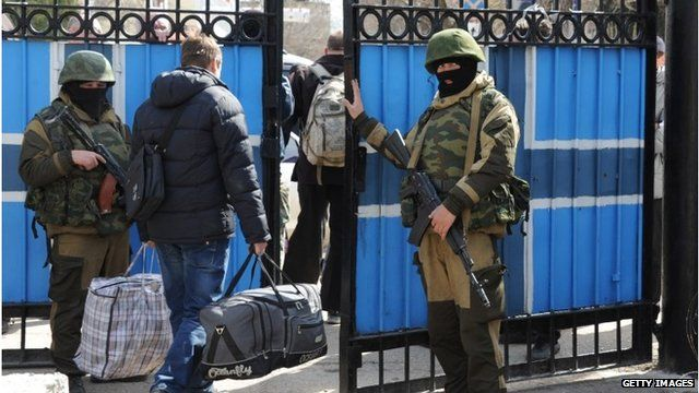 Ukrainian officers leave as Russian soldiers patrol at the Ukrainian navy headquarters