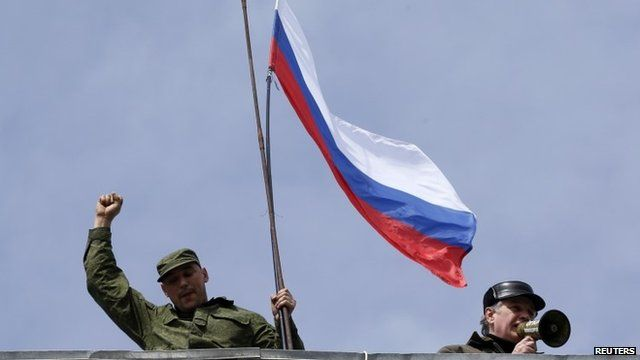 A man holds a Russian flag on the roof of the naval headquarters in Sevastopol