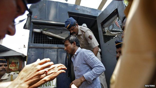Police escort one of the accused men to court