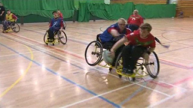Members of wheelchair rugby club in training