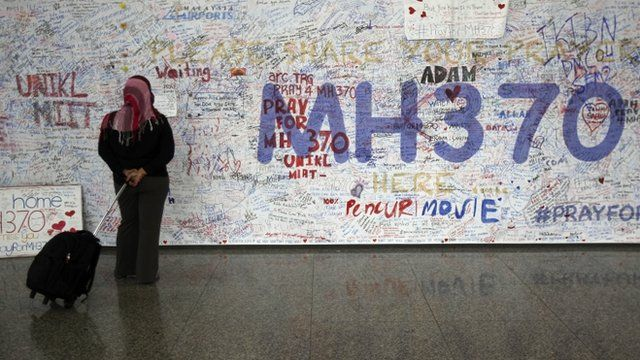 A woman reads messages for passengers aboard a missing Malaysia Airlines plane
