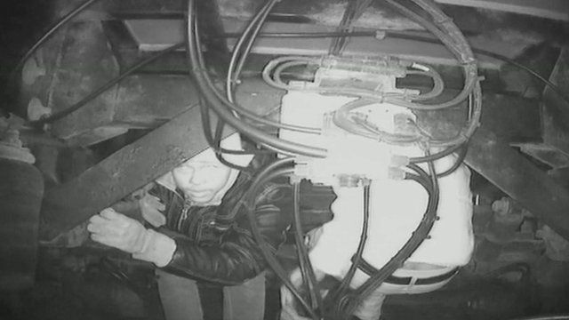 A night vision camera catches two men attempting to sit on the axle of a lorry to get into the UK