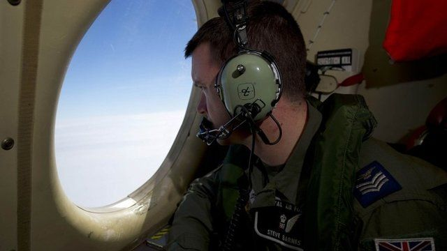 Royal Air Force Sergeant Steve Barnes looks out of an observation window on a Royal Australian Air Force