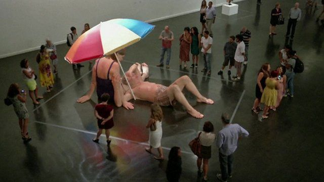 Crowds gathered around a Ron Mueck sculpture