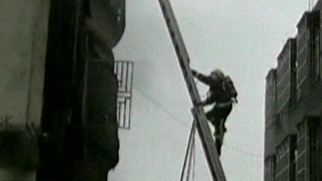 A fireman climbs a ladder outside the factory