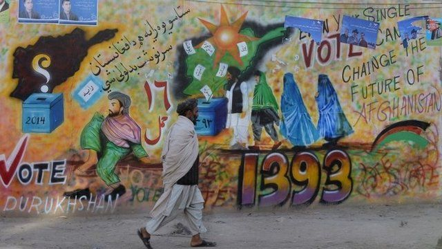 A man walks past an election themed mural in Kandahar, Afghanistan, 30 March 2014