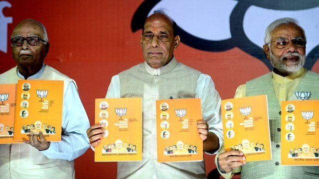 """India""""s Bharatiya Janata Party (BJP) Prime Ministerial candidate Narendra Modi poses with the party manifesto"""