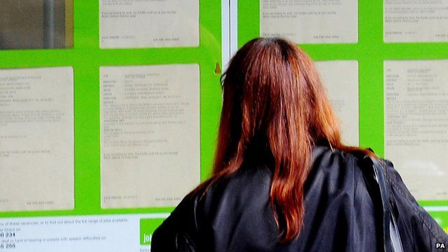 Woman looking posters in a job centre