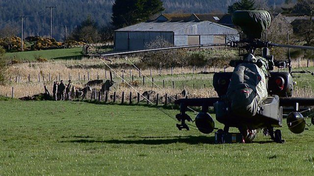 Troops guard an army Apache helicopter