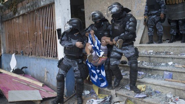 Police officers carry a squatter during an eviction from an abandoned building in Rio de Janeiro, Brazil