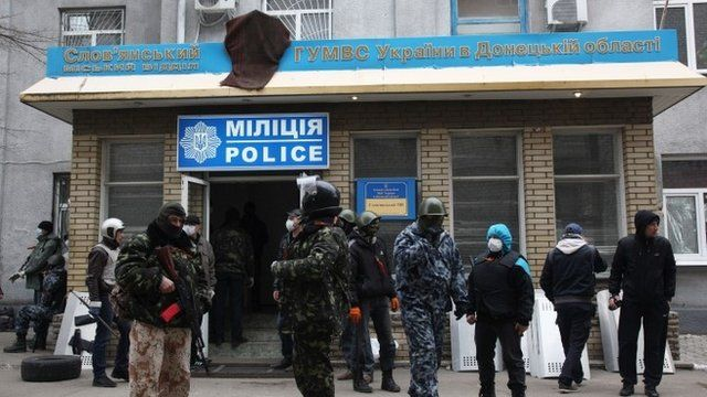 Armed pro-Russian activists guard a police station in the eastern Ukrainian city of Sloviansk after it was seized