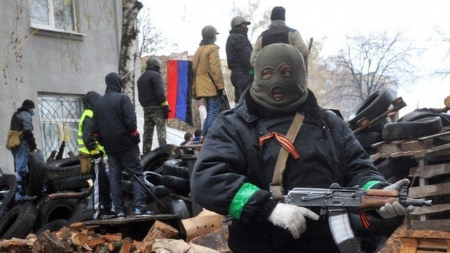Pro-Russia protesters guard a barricade outside a regional police building seized by armed separatists in Sloviansk