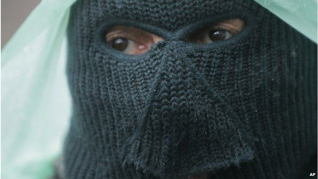 A pro-Russian gunman stands guard at a seized police station in the eastern Ukraine town of Sloviansk