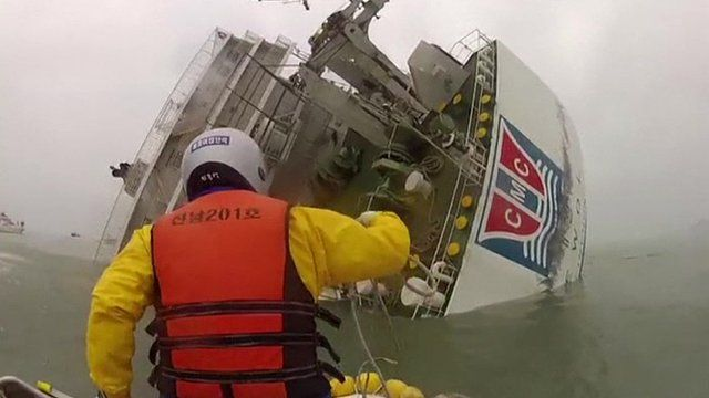 A rescue ship approaches a sinking ferry