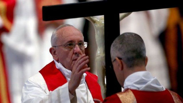 Pope Francis kisses the cross as he attends a Papal Mass with the Celebration of the Lord's Passion inside St Peters Basilica on April 18