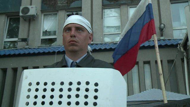 A man with a shield stands in front of a Russian flag