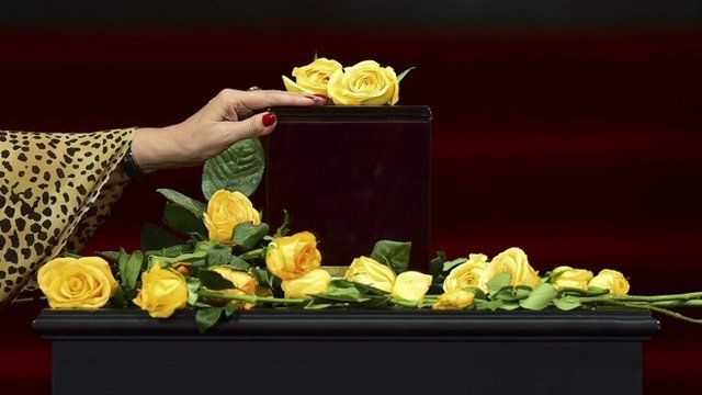 A woman touches the urn containing the ashes of Gabriel Garcia Marquez