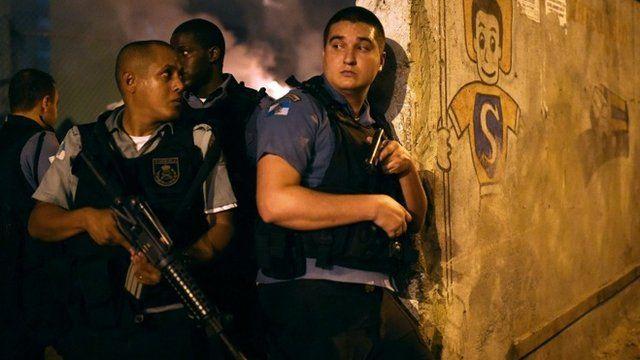 Rio de Janeiro's state military policemen stand in position during a violent protest in a favela next to Copacabana, Rio de Janeiro on April 22, 2014