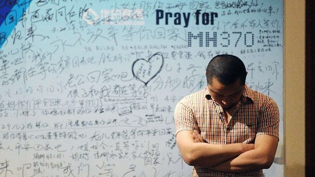 man stands in front of a billboard in support of missing Malaysia Airlines flight MH370