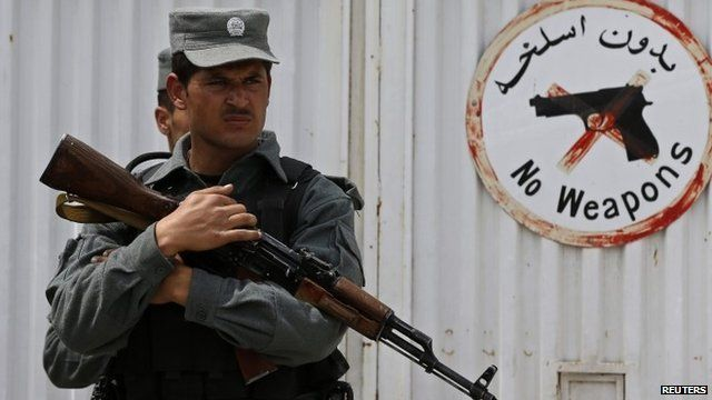 An Afghan policeman stands at the gate of Cure Hospital after three Americans were killed in Kabul April 24, 2014