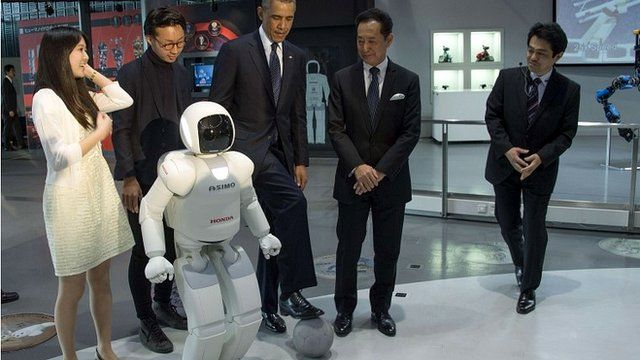 President Obama positions a football next to robot