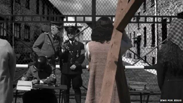 A still from the video showing Jesus holding a cross at a Nazi extermination camp.