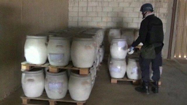 A OPCW operative checks barrels