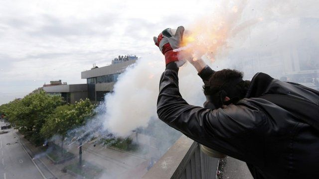 A protester shoots firecrackers at riot police during a May Day demonstration in Istanbul May 1, 2014